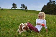 嬉戏的狗和妇女在草甸 免版税库存照片