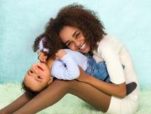 嬉戏的非洲母亲和婴孩 免版税库存照片