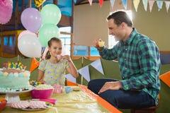 嬉戏的食用女孩和的父亲从被设置的玩具厨房的茶 免版税库存照片