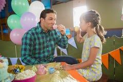 嬉戏的食用女孩和的父亲从被设置的玩具厨房的茶 库存照片