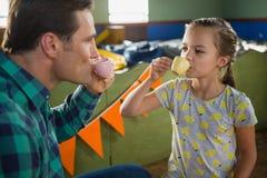嬉戏的食用女孩和的父亲从被设置的玩具厨房的茶 免版税库存图片