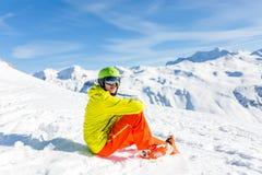 嬉戏穿救生服的人佩带的盔甲照片坐多雪的倾斜 免版税图库摄影