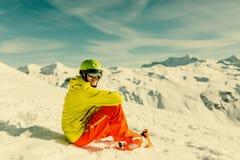 嬉戏穿救生服的人佩带的盔甲的图象坐多雪的倾斜 免版税库存照片