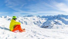 嬉戏穿救生服的人佩带的盔甲的图象坐多雪的倾斜 免版税库存图片