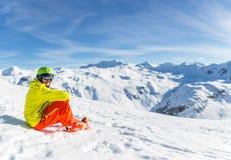 嬉戏穿救生服的人佩带的盔甲的图象坐多雪的倾斜 免版税图库摄影