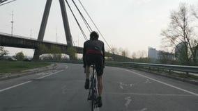 嬉戏适合的有桥梁的triathlete乘坐的自行车在背景 训练三项全能种族的 r 股票录像