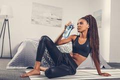 嬉戏非裔美国人的在锻炼以后的妇女饮用水在家 免版税库存图片