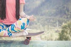 嬉皮做瑜伽的时尚女孩,放松在滑板在山 免版税库存图片