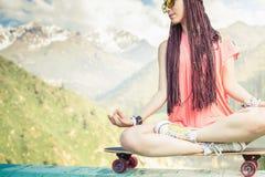 嬉皮做瑜伽的时尚女孩,放松在滑板在山 库存图片