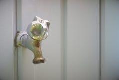 子口在灰色墙壁,阀门上的自来水 免版税库存图片