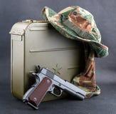 子弹、枪和一个被伪装的帽子的箱子 免版税库存照片