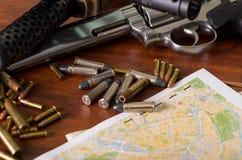 子弹和火器 子弹是从一个火器的桶逐出的子弹头在一张地图的,在木桌上 免版税库存图片