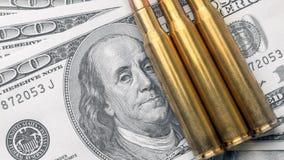 子弹在100美元票据的特写镜头谎言  拷贝空间货币和国防的概念 库存照片