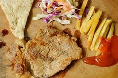 以子弹密击与法语油煎的和沙拉的猪肉牛排在剁块 图库摄影