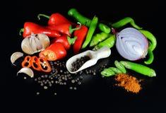 以子弹密击红色、绿色和豌豆与一棵木匙子、大蒜和葱 库存照片