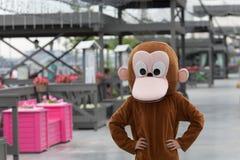 猴子服装的一个人在街道上站立 库存照片