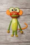 猴子由新鲜蔬菜做成在木背景 库存图片