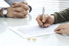 妻子签署离婚与圆环的旨令形式 免版税库存图片