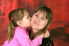 子项亲吻母亲 库存图片