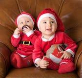 子项克劳斯给圣诞老人穿衣 免版税库存图片