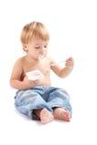子项吃酸奶 免版税图库摄影