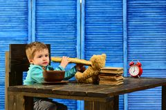 子项在幼稚园 小孩吃法国长方形宝石 孩子享受坐在桌上的鲜美晚餐 孩子的鲜美食物 库存照片