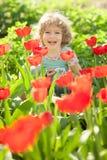 子项在用花装饰的庭院里 免版税库存图片