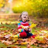 子项在秋天公园 与秋叶的孩子 免版税库存图片