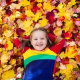 子项在秋天公园 与秋叶的孩子 免版税库存照片