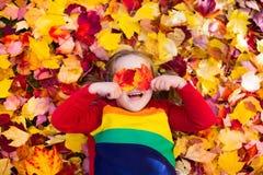 子项在秋天公园 与秋叶的孩子 免版税图库摄影