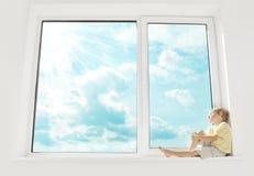 子项坐视窗,享受阳光 免版税库存照片