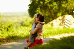 子项她拥抱的母亲室外年轻人 免版税图库摄影