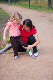 子项她的放置鞋子的母亲 图库摄影