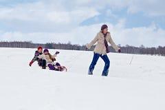 子项帮助母亲他们骑马的雪橇 图库摄影