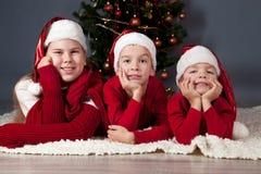 子项是在圣诞树附近。 免版税库存图片