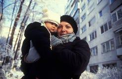 子项穿戴的母亲冬天 库存图片