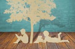 子项纸张剪切在结构树下。 免版税图库摄影
