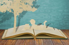 子项纸张剪切读了一本书 免版税图库摄影