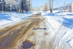孔和坑洼一条农村路的有雪的 免版税库存图片