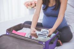 孕妇一些材料为她做准备新出生 免版税库存照片