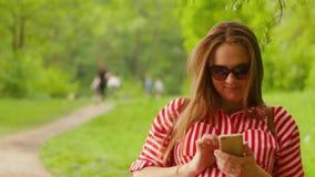 孕妇举行电话在一只手,迅速类型消息上,停留公园 ?? 股票视频