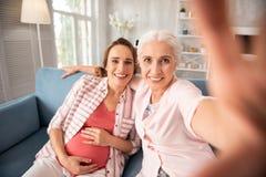 孕妇佩带的镶边衬衣坐沙发在她的老朋友附近 库存图片