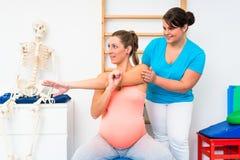 孕妇做舒展与理疗师的锻炼 免版税图库摄影