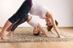 孕妇和一点女儿瑜伽行使 库存照片