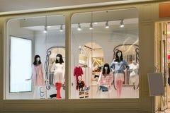 孕妇和儿童时装模特在时尚商店窗口里 免版税库存照片
