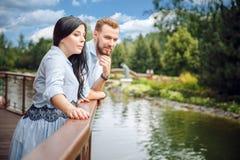 孕妇和她的丈夫在水拥抱附近的一个公园 图库摄影