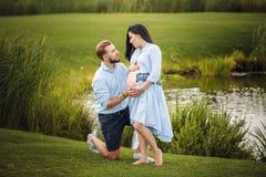 孕妇和她的丈夫在水拥抱附近的一个公园 免版税库存图片