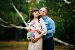 孕妇和她英俊的丈夫可爱放松在自然,有野餐在公园 免版税图库摄影