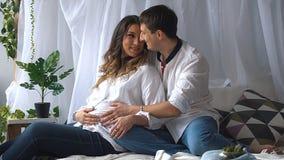 孕妇和她英俊的丈夫微笑着 免版税库存图片