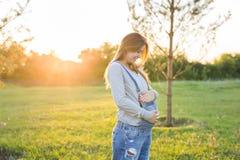 孕妇在公园,感人的腹部 库存图片